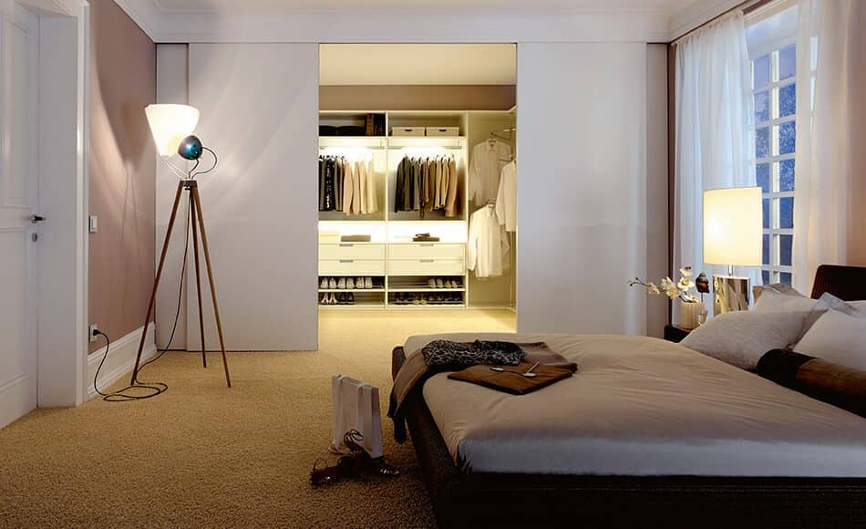 The picture depicts a bedroom, at the rear of which is a walk-in wardrobe by Ars Nova Collection which can be closed with Delta sliding doors.