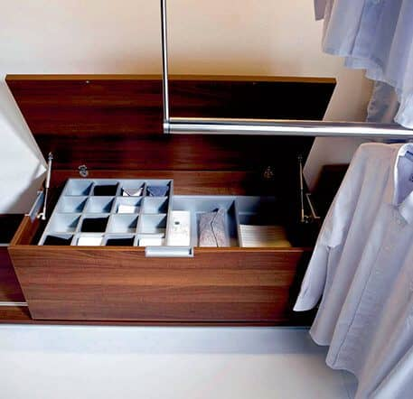 The picture shows part of a Beta Nova wardrobe. It is a wooden chest with storage compartments containing accessories and items of clothing. There are shirts hanging on a clothes rail on the right side.