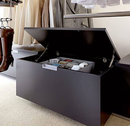 This picture depicts a drawer from the Beta Nova series in a wardrobe, the lid of which is half open, and there is a compartment with belts and ties in the chest. Around it are clothing rails on which clothing is hanging.