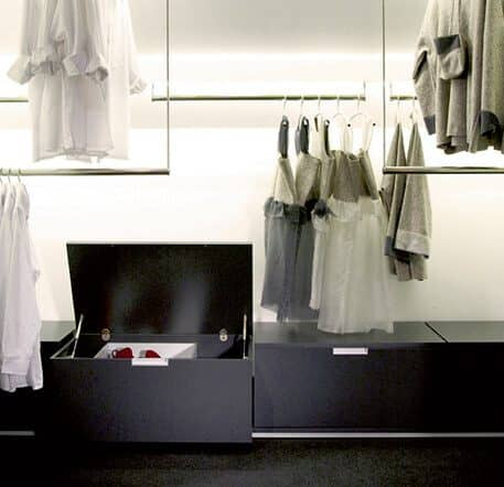 The picture depicts a Beta Nova walk-in wardrobe with black, extractable drawers on a floor track and hanging clothes rails. Indirect lighting ensures pleasant lighting.