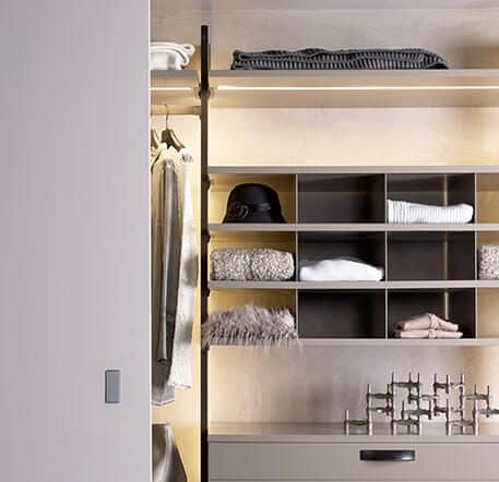 Das Bild zeigt das beleuchtetes Kleiderschrankelement Centric mit Schubladen, Fächern, Ablageflächen und einer Kleiderstange. Links ist eine Schiebetür zu sehen.
