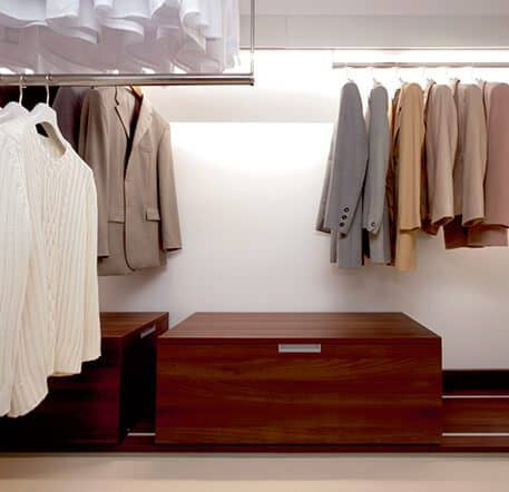 The picture depicts the interior of the walk-in Beta Nova wardrobe which includes large wooden chests on rails to store items and flexible clothes rails.