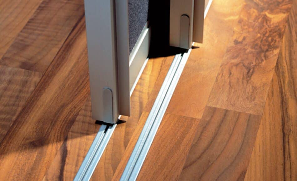 The picture depicts two sliding doors of Ars Nova Collection on floor tracks.