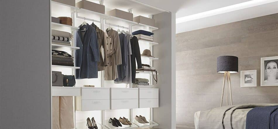 The picture depicts a bedroom in which an open, illuminated Centric shelving system with drawers, storage areas and clothes rails fits perfectly into a niche.
