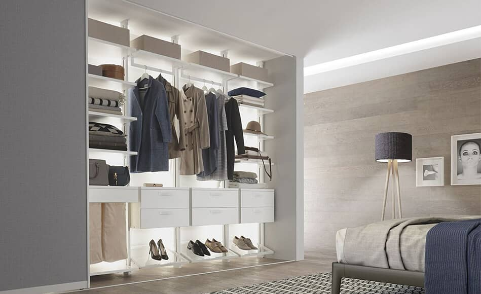 The Picture Depicts A Bedroom In Which An Open, Illuminated Centric  Shelving System With Drawers