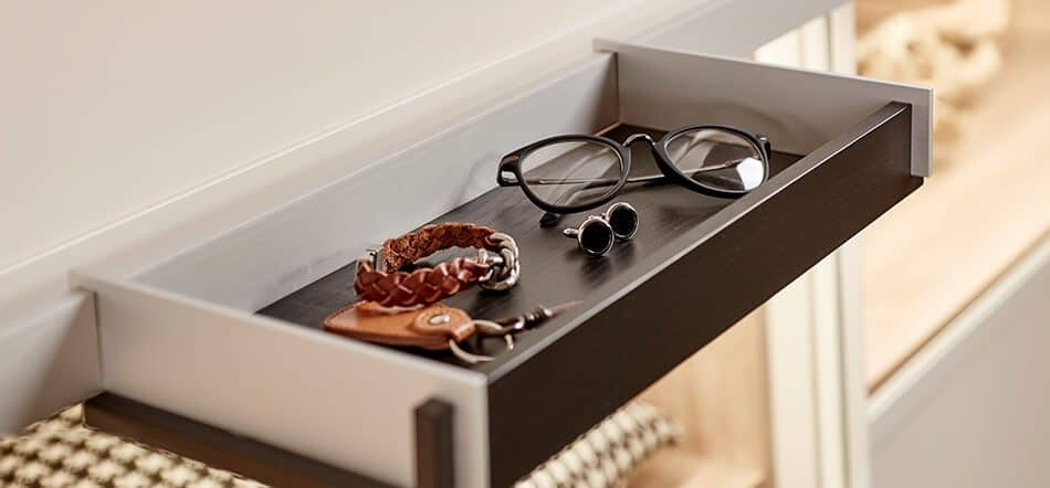 The picture depicts a storage compartment which is part of a shelving system. It contains a pair of glasses, a bracelet, earrings and a key ring.