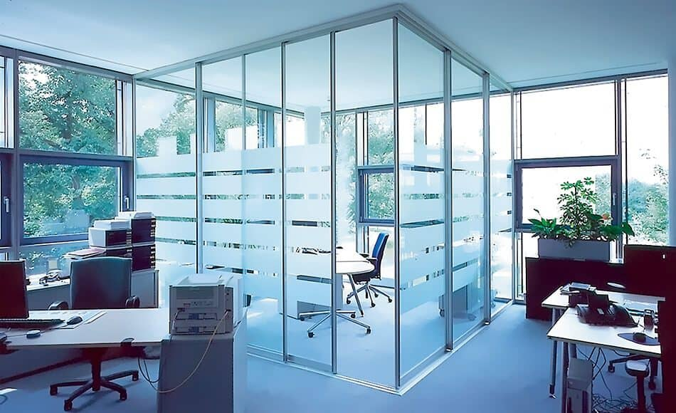 The picture depicts an office with several desks. A part of the office is partitioned off from the rest with a Delta sliding door element.