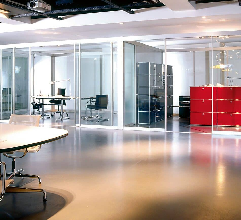 The picture depicts a large room with offices running off it which are partitioned by room dividers made by Ars Nova Collection.