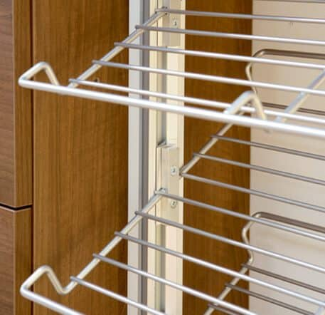 The picture depicts the aluminum stands of the Quattro Plus walk-in wardrobe, to which a shoe rack is fixed. A brown cabinet is visible in the background.