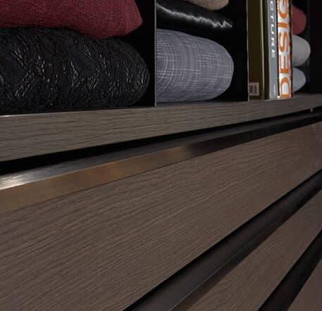 The picture depicts the drawers of the walk-in wardrobe Walk_in by Ars Nova Collection in grey brown. The handle strip is made of brushed aluminum.