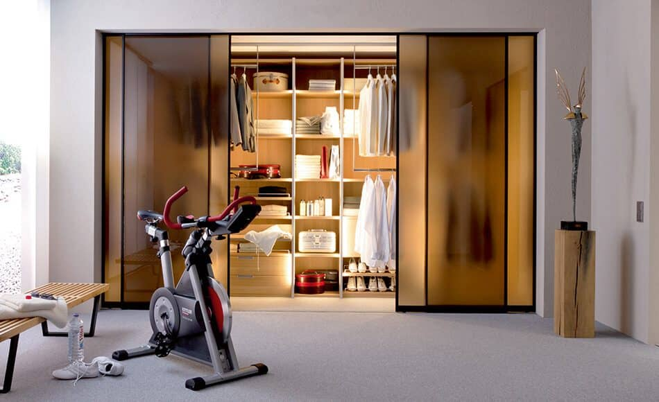 The picture depicts a fitness room; there is a Beta Nova wardrobe integrated into the rear of it. The wardrobe contains shirts, towels, suitcases and transport boxes, and can be closed with the help of sliding doors.