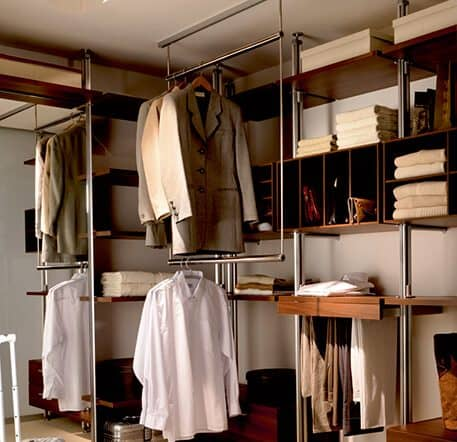 The picture depicts a walk-in Beta Quattro wardrobe whose drawers and storage elements were kept in a middle brown color. There is clothing hanging and lying in the wardrobe.