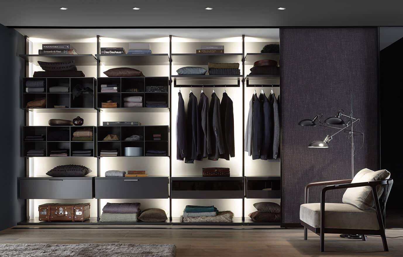 This picture depicts a living room with a shelving system that contains many compartments and offers several options to store clothing.