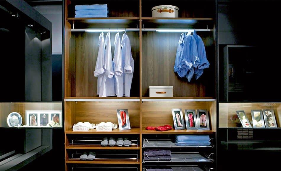 Hier ist der Beta-Quattro-Kleiderschrank in mittelbraunem Holz zu sehen. Der beleuchtete Innenraum sorgt für eine klare Sicht auf alle Kleidungsstücke.