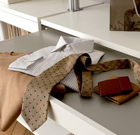 The picture depicts a storage area of the Beta Quattro shelving system on which there is a brown pullover, a striped shirt, a brown tie and a leather purse.