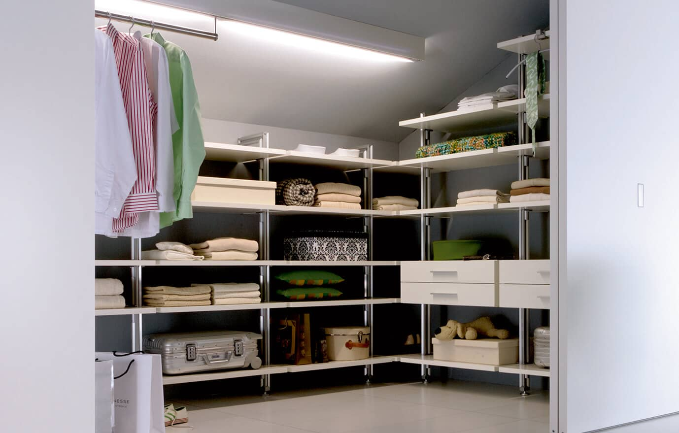 The picture depicts a Quattro Plus walk-in wardrobe of Ars Nova Collection which can be partitioned off with a white sliding door.