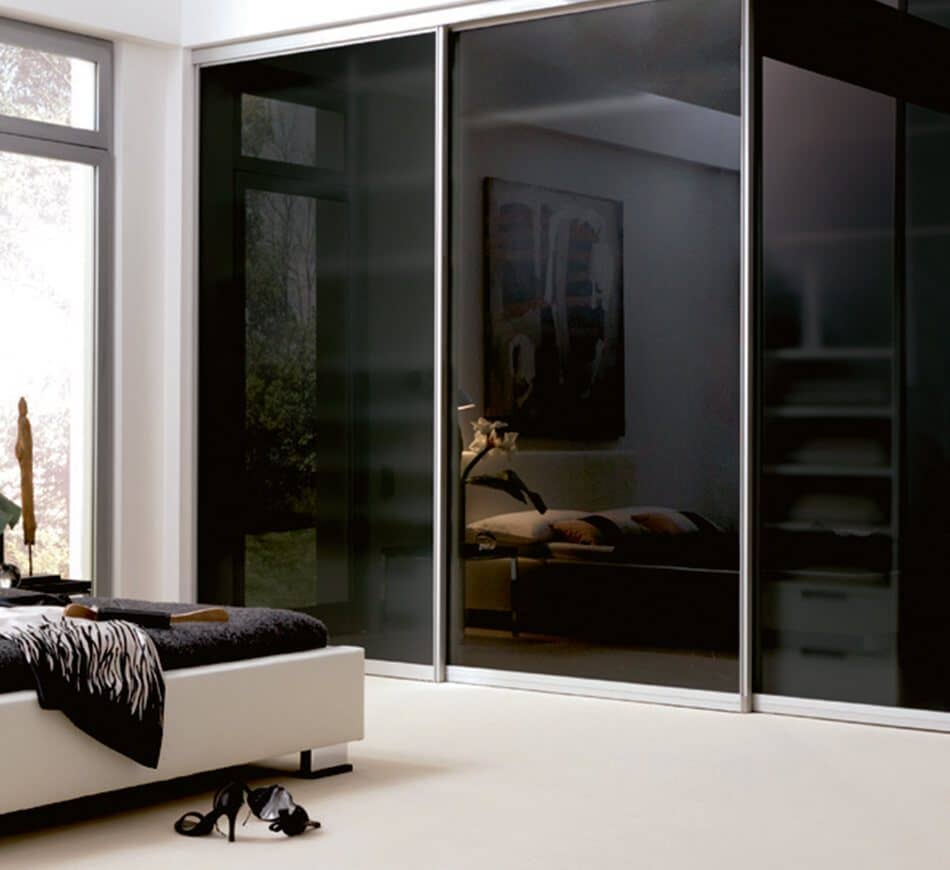 This picture depicts a built-in cabinet with high-gloss black doors which is standing in a bright bedroom.