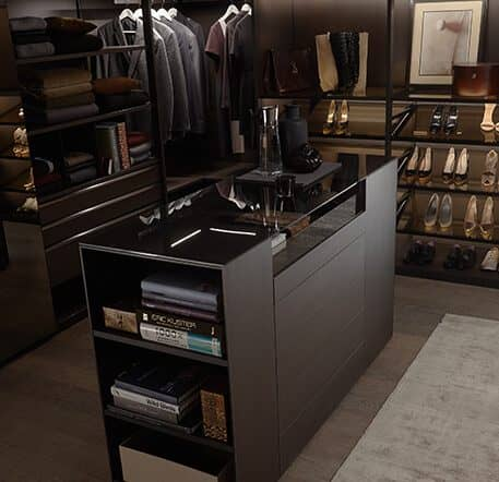 The picture depicts a walk-in wardrobe Walk_in by Ars Nova Collection. It stretches across the corner and in the middle there is a matching cabinet containing books and other items.