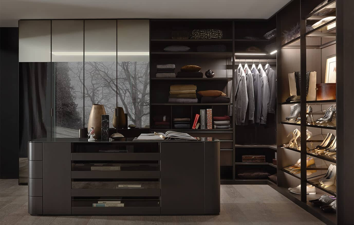 The picture depicts a walk-in wardrobe from the Walk_in range by Ars Nova Collection with a cabinet in the middle, a mirrored cabinet and an open illuminated element which extends past the corner.