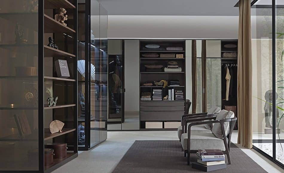 The picture depicts a walk-in wardrobe Walk_in by Ars Nova Collection with glass cabinets. On the right of the picture, there is a rug, two armchairs and a pile of books.