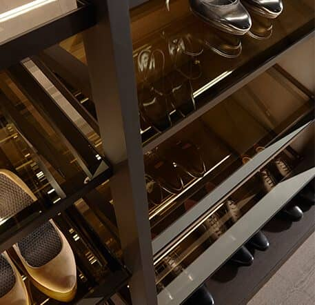 The picture depicts the shoe rack from the Ars Nova Collection Walk_in shelving system. The shelves are made of glass and the frame of aluminum.