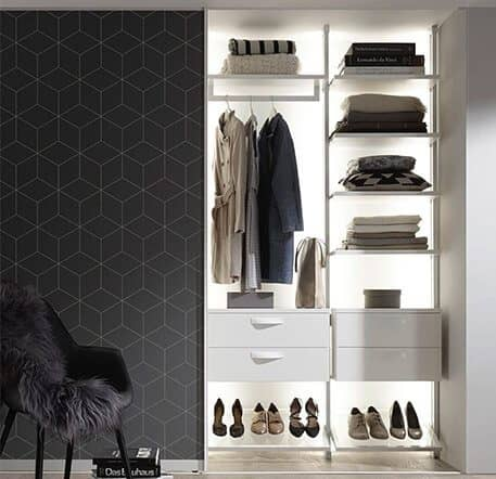 A room with a wardrobe in which clothing is neatly stowed and an armchair.