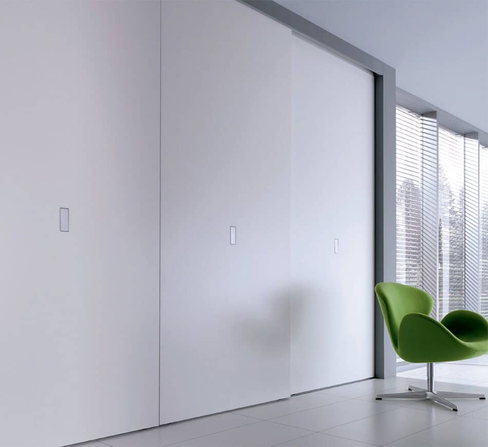 The picture depicts a living space brightened by large windows, in the front of which are large Beta Quattro sliding doors in a niche.