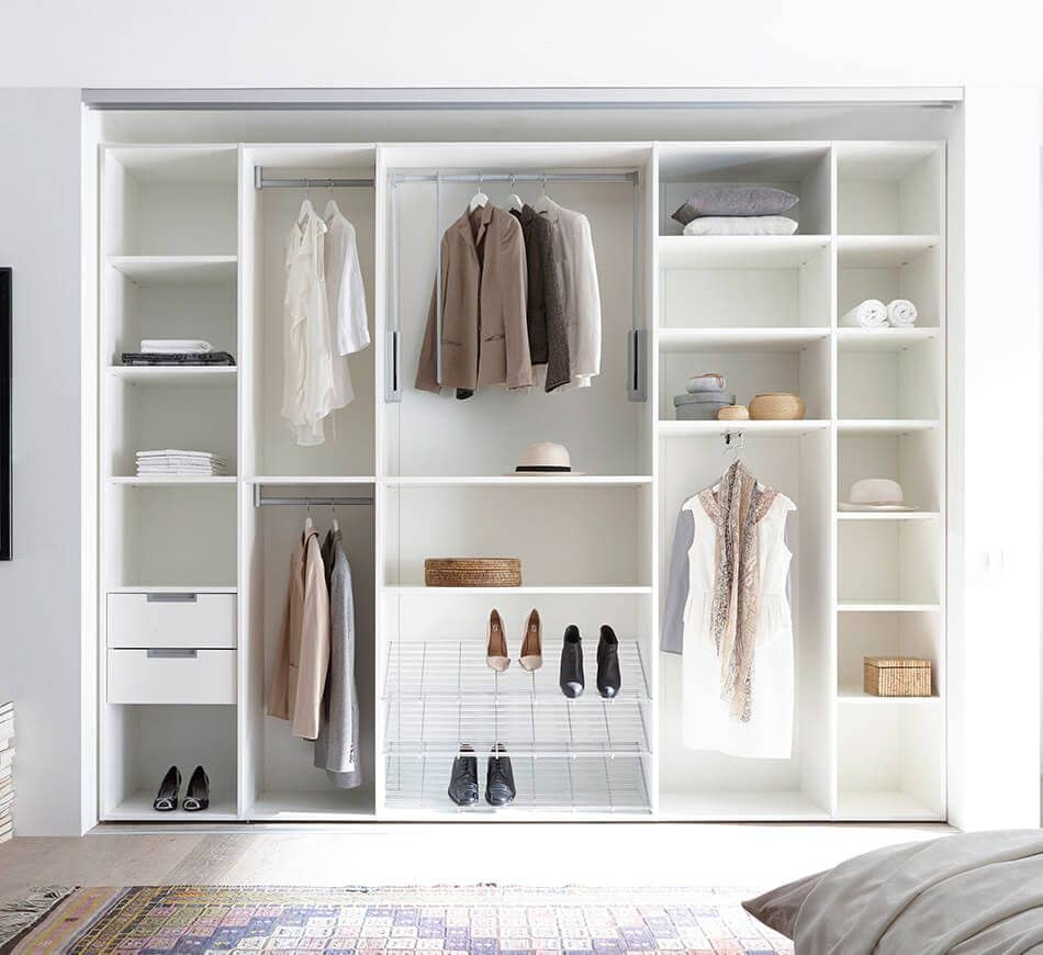 The picture depicts an open, white, built-in wardrobe in a bedroom containing drawers, storage shelves, shoe racks and compartments. It contains women's clothing.