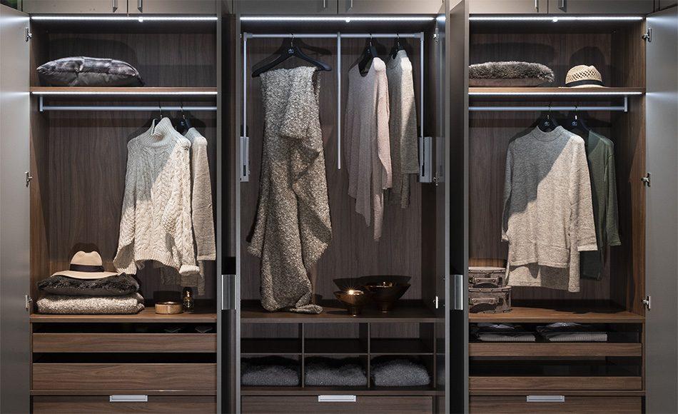 Hier ist der Drehtüren-Kleiderschrank in Nussbaum_Dekor zu sehen. Der beleuchtete Innenraum sorgt für eine klare Sicht auf alle Kleidungsstücke.